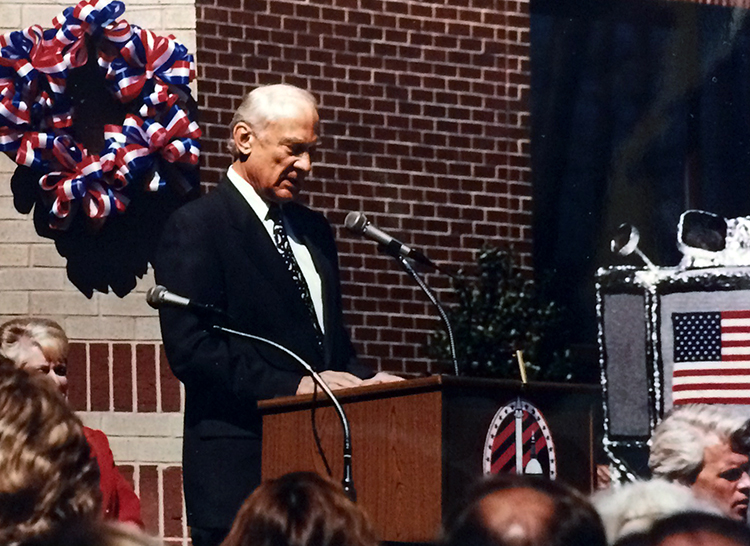 Photograph of Buzz Aldrin standing at a podium delivering his remarks at Aldrin Elementary School's dedication ceremony.