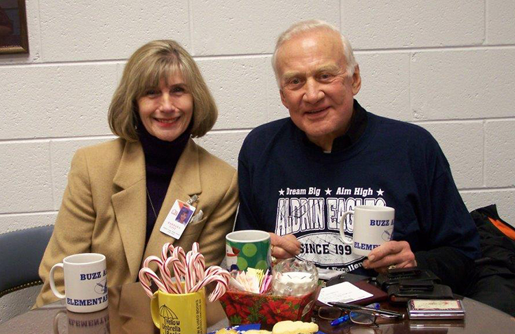 Photograph of Assistant Principal Barbara Gist with Dr. Buzz Aldrin. They are seated at a small table that has food in the center. Dr. Aldrin is wearing an Aldrin Eagles shirt.
