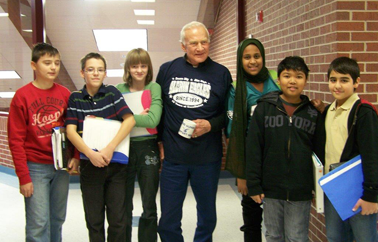 Photograph of Buzz Aldrin standing with a group of nine smiling students.