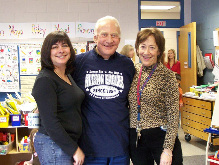 Photograph of teachers Mrs. Harrison and Mrs. Keyser posing with Dr. Buzz Aldrin. They are standing in a classroom and two adults and a child are visible in the doorway behind them.