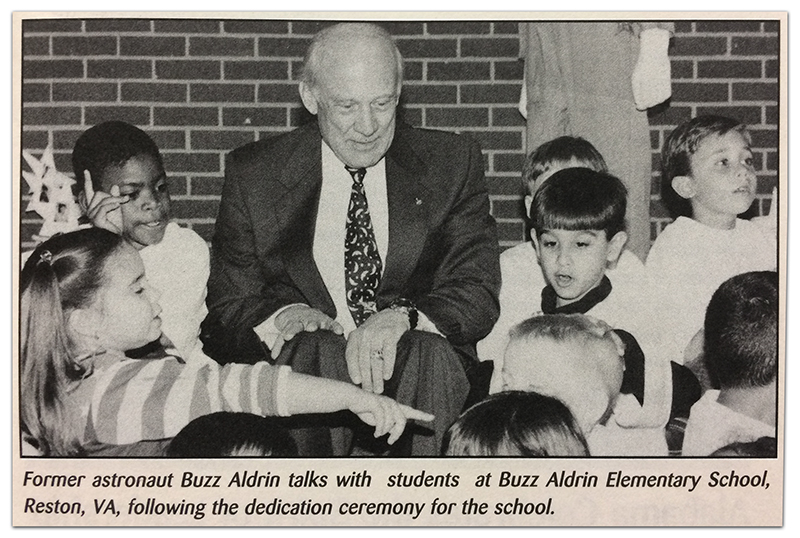 Newspaper clipping from a Herndon Observer newspaper article covering the dedication of Aldrin Elementary School. There is a black and white photograph of Buzz Aldrin seated with a group of some nine students. They are engaged in conversation. The caption reads: Former astronaut Buzz Aldrin talks with students at Buzz Aldrin Elementary School, Reston, Virginia, following the dedication ceremony for the school.