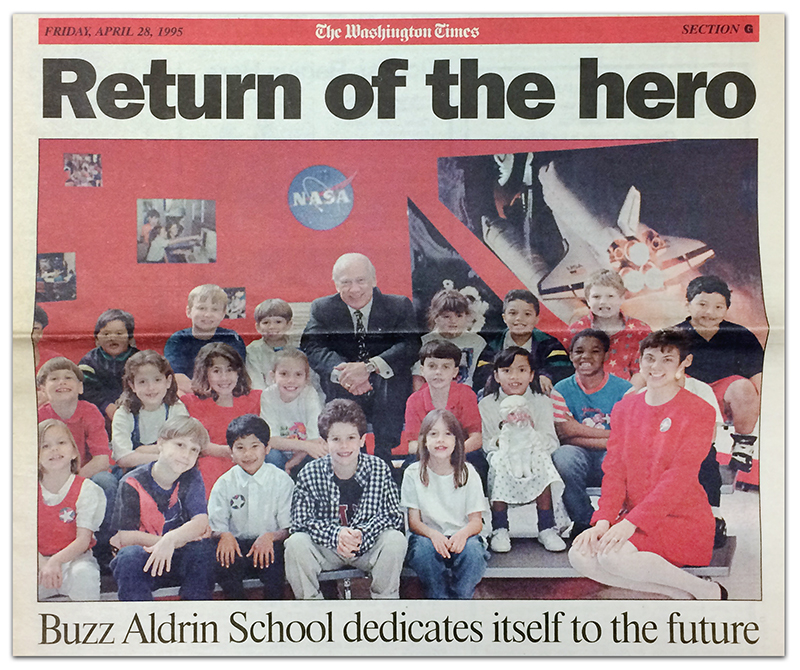 Newspaper clipping of the cover of the Washington Times newspaper from April 28, 1995. The headline reads: Return of the Hero, Buzz Aldrin School dedicates itself to the future. A large color photograph is beneath the headline. It shows Buzz Aldrin seated with a group of 20 students and their teacher on metal risers. On the wall behind them are photographs of a Space Shuttle, children at computers, and the NASA logo.