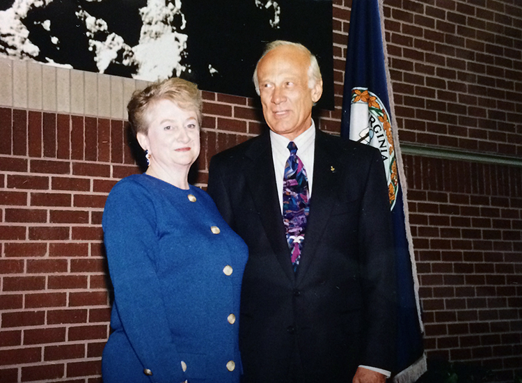 Photograph of Aldrin Elementary School Principal Gina Ross and Buzz Aldrin. They are standing side-by-side on the small raised platform inside the school lobby. A Virginia flag is visible behind Aldrin.