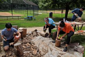 Brightspot volunteers helps to sand and prepare stumps to be used for student seating in the outdoor classroom.